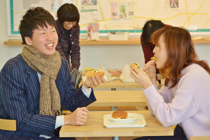 「いがねこ特製!伝統小松菜ソースのポテトドッグ」を美味しそうに頬張る学生